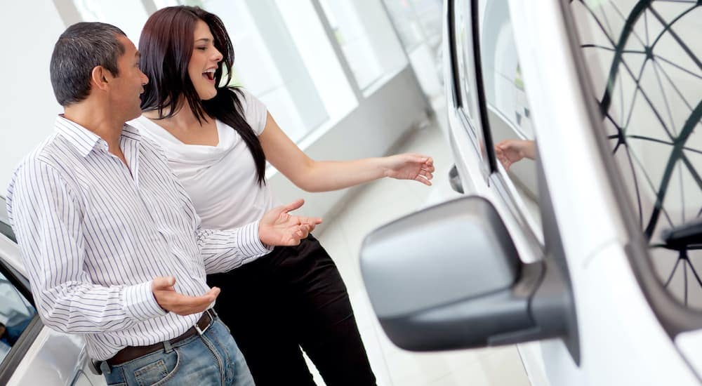 An excited couple is shown looking for cars at a used car dealer in Lexington.
