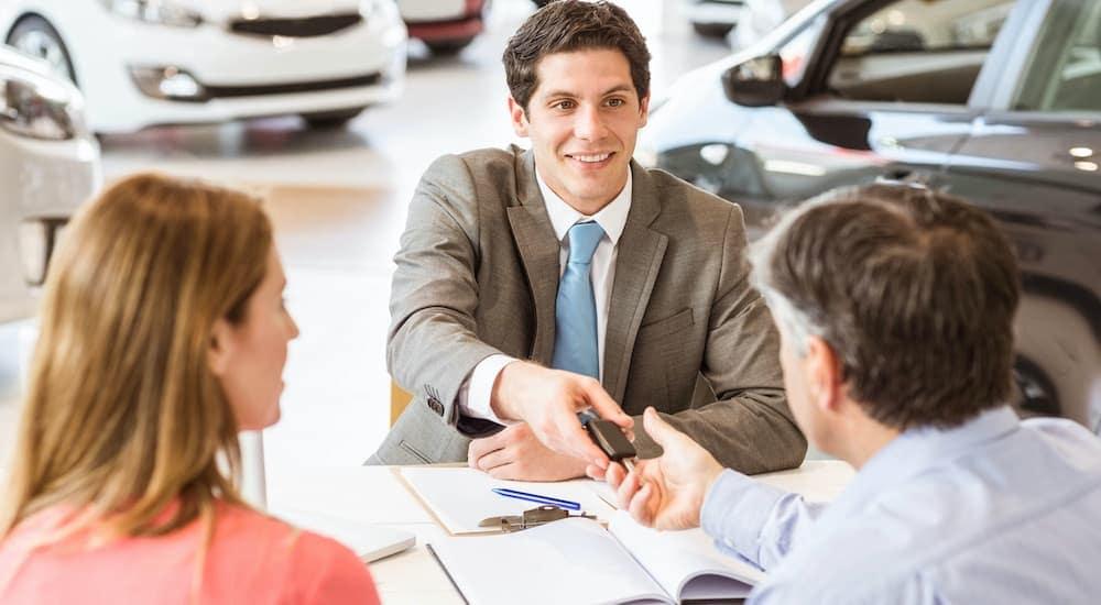 A close up shows a sales man handing a set of car keys to a couple.