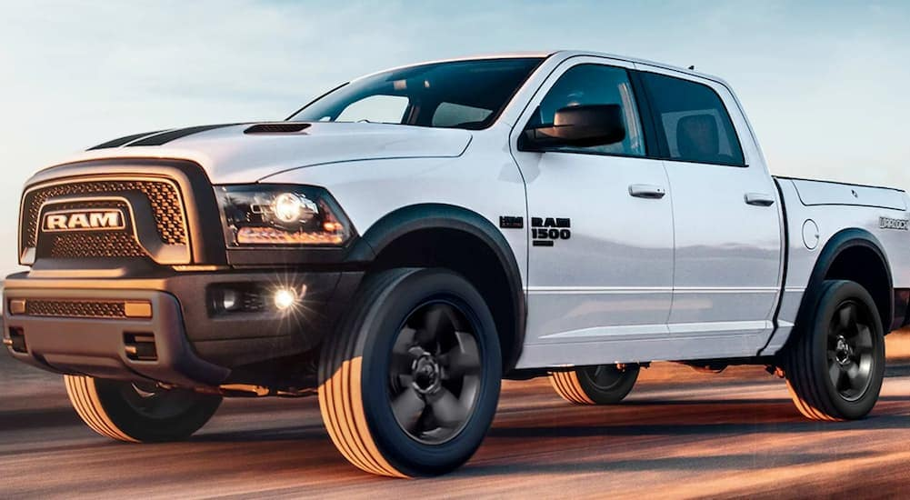 A white 2019 Ram 1500 Classic, a popular used Ram truck in Lexington, is driving on a highway.