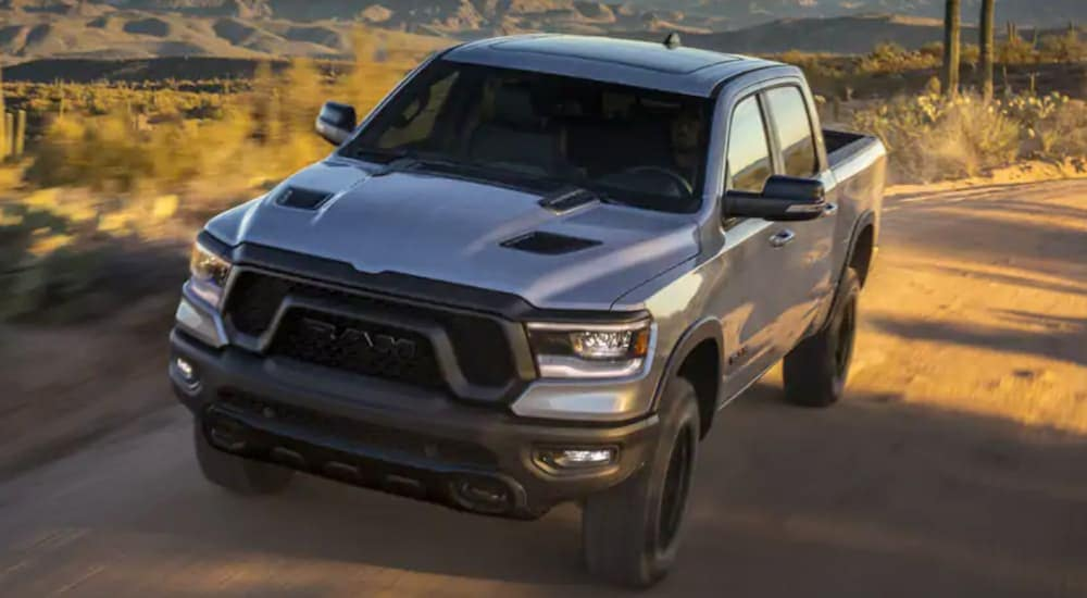 A grey 2021 Ram 1500 is driving on a desert road.
