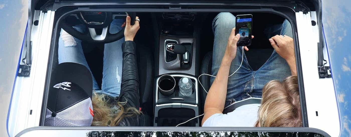 The black interior and passengers are shown from a high angle through the sunroof or a 2021 Dodge Charger.