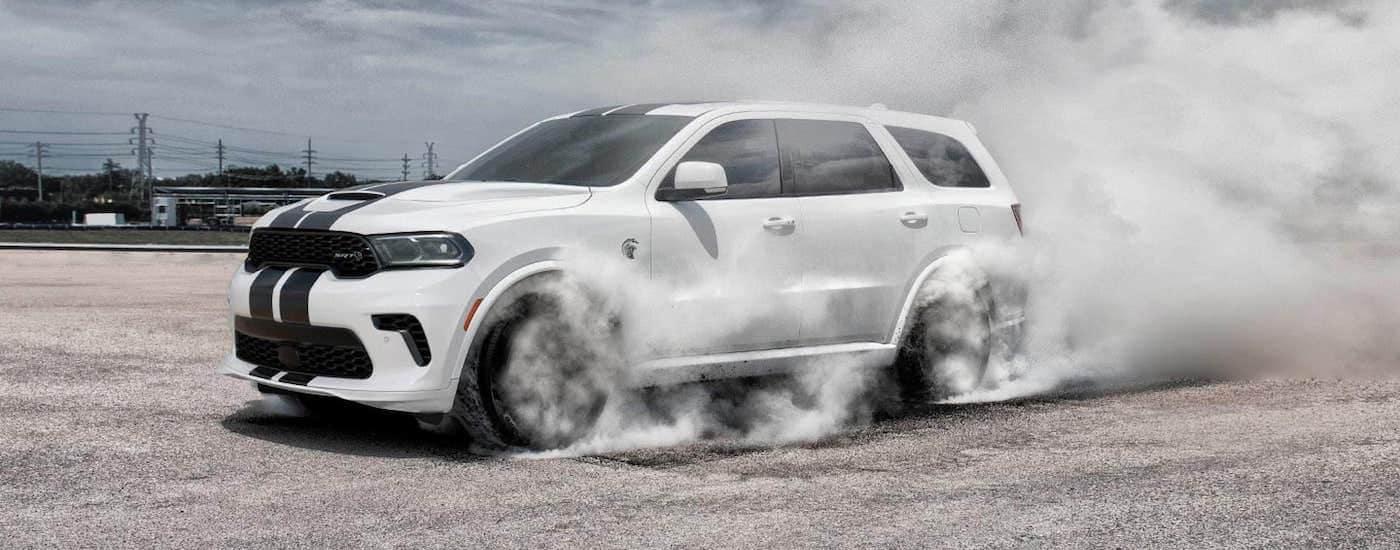 A white 2021 Dodge Durango SRT is in an empty parking lot doing a burnout.