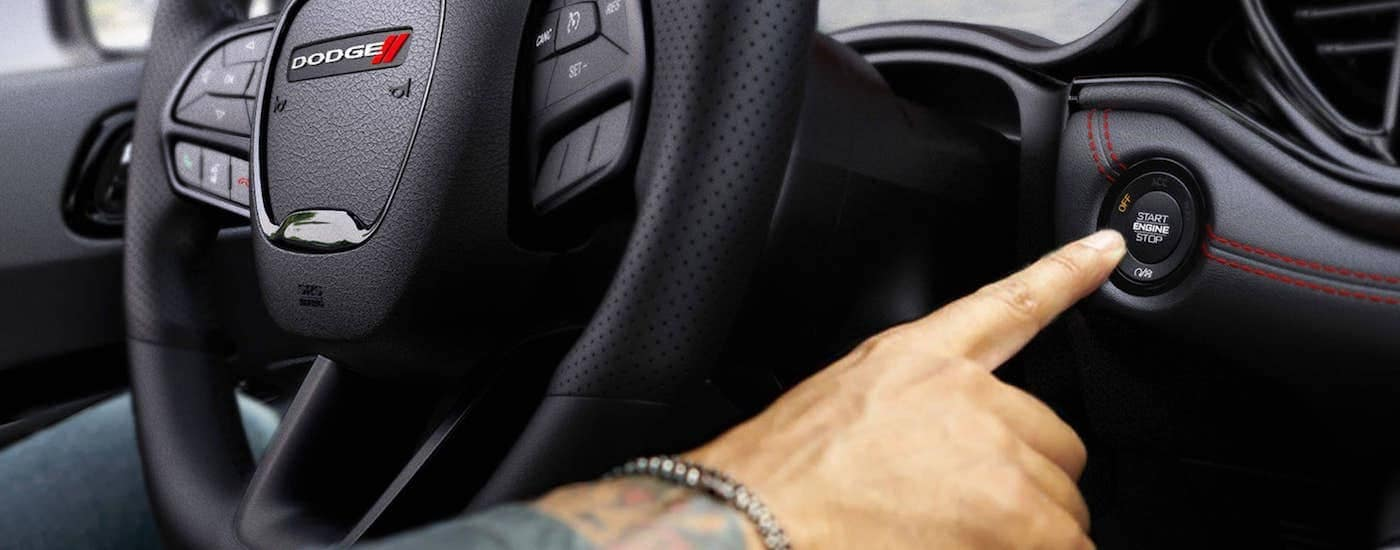 The black interior is shown with a man pressing the push-button start in a 2021 Dodge Durango.