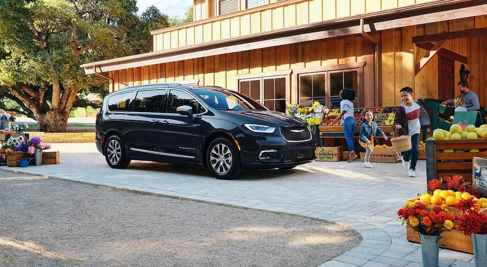 A black 2021 Chrysler Pacifica Hybrid is shown from the side, parked at a farmers market.