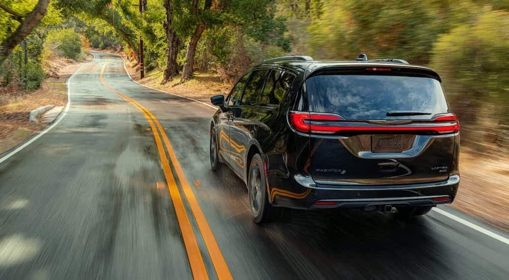 A black 2021 Chrysler Pacifica Limited, from a Chrysler dealer near me, is shown from the rear speeding down a tree-lined road.