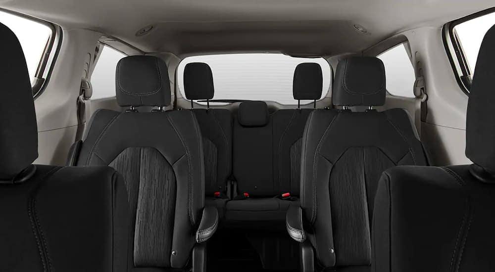That black interior and rear seating is shown in a 2021 Chrysler Voyager.