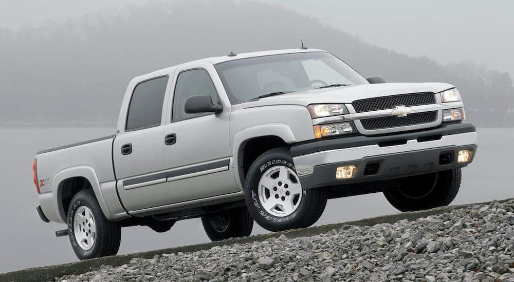 A silver 2004 Chevy Silverado 1500 is shown from the side parked on a misty road.