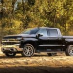 A black 2019 Chevy Silverado 1500 is shown from the side parked on a dirt tract with dust in the air.
