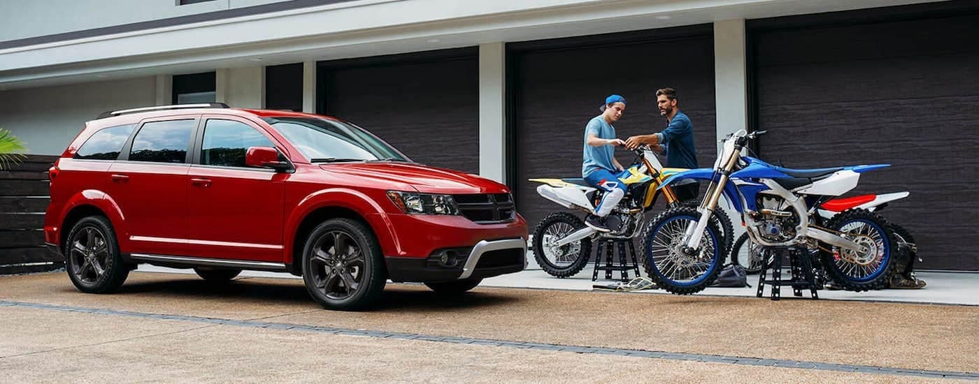 A red 2020 Dodge Journey is shown from the side parked next to a couple dirt bikes and garage.