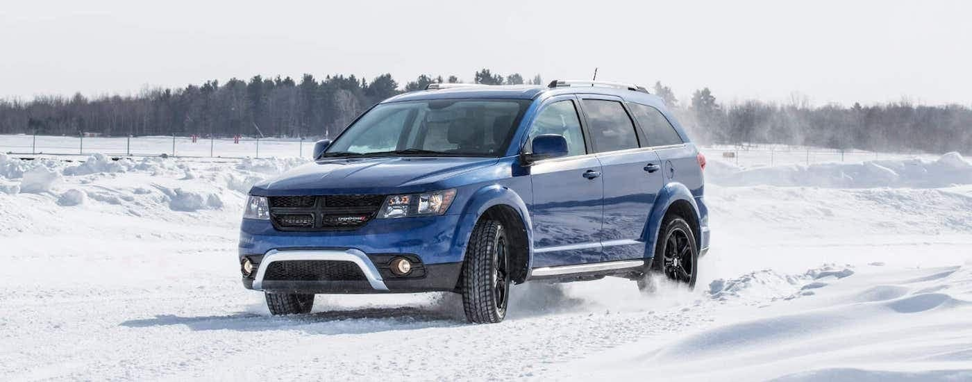 A blue 2020 Dodge Journey is driving past a fence on a snowy road.