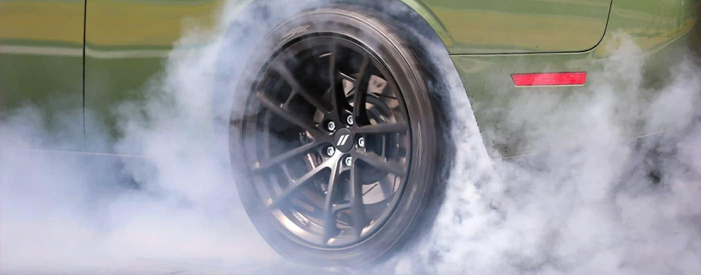 A close up shows the black wheel on a green 2021 Dodge Challenger doing a burnout.