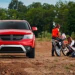 A red 2020 used Dodge Journey is shown from the front, parked next to a dirtbike.