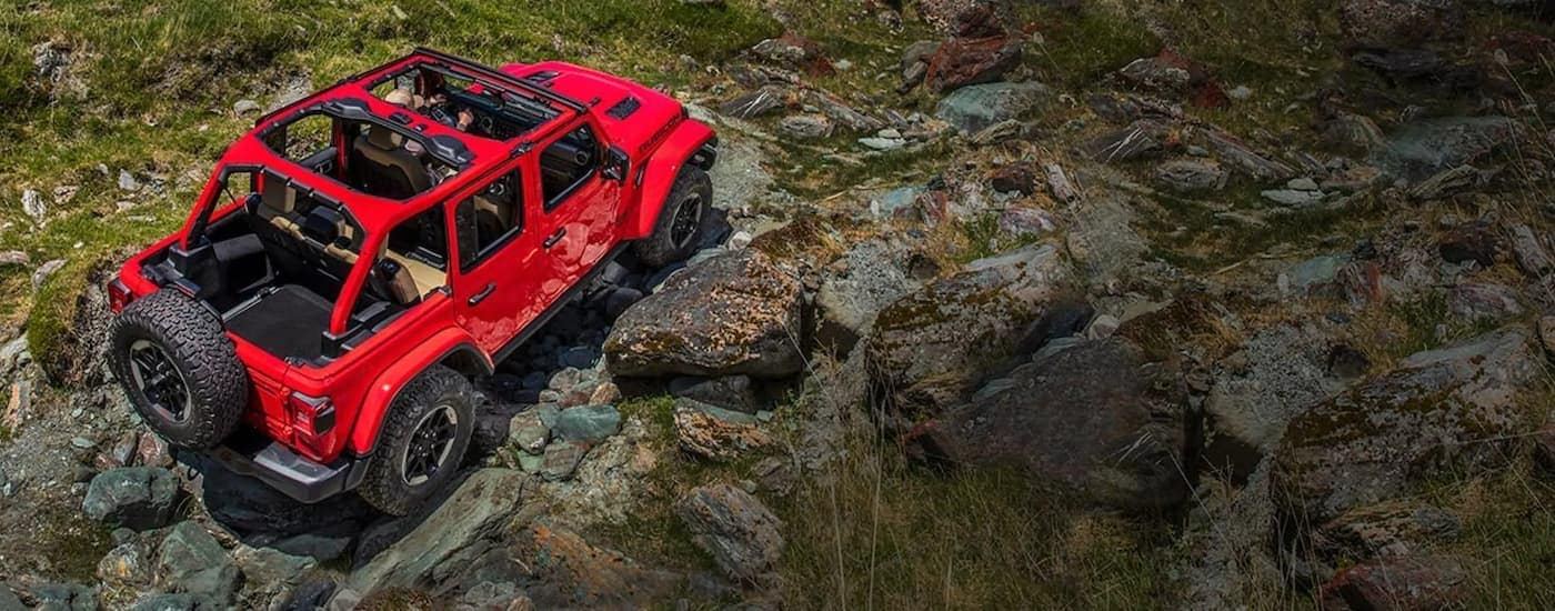A red 2019 used Jeep Wrangler Rubicon with no roof is shown from above off-roading on rocky terrain.