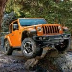An orange 2019 used Jeep Wrangler Rubicon is off-roading in the woods.