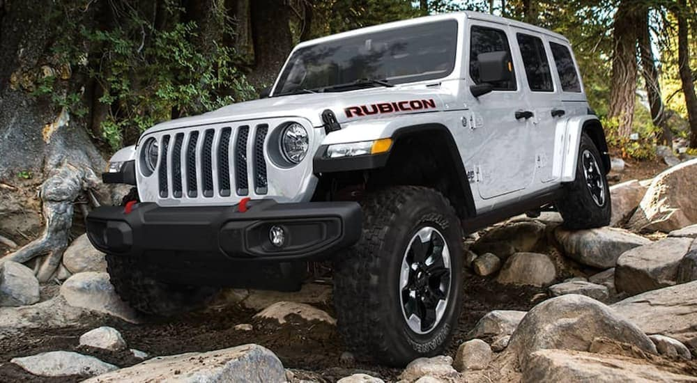 A white 2020 used Jeep Wrangler Rubicon is off-roading on a rocky trail.