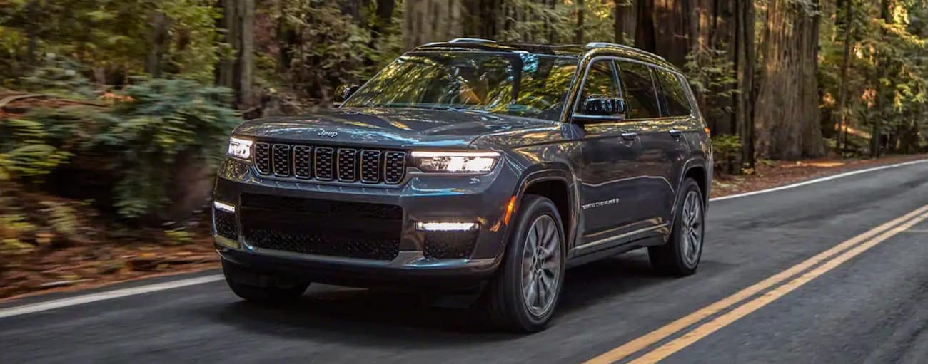 A grey 2021 Jeep Grand Cherokee L is driving on a tree-lined road.