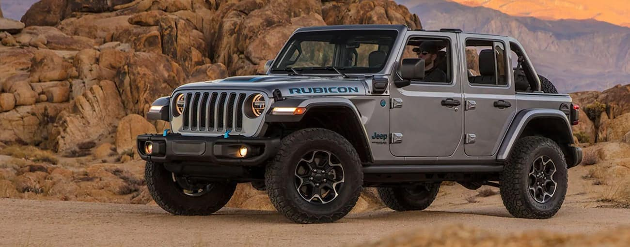 A grey 2021 Jeep Wrangler 4xe is parked in front of desert rocks.