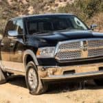 A black 2017 Ram 1500 is shown from the front parked on a dirt path.
