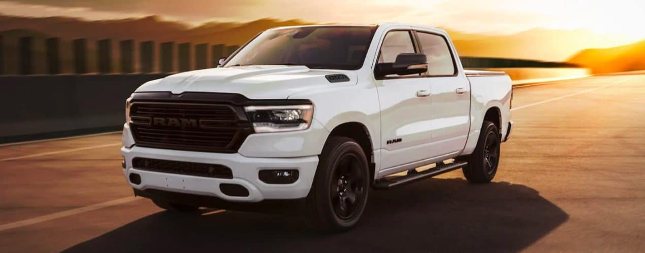 A white 2021 Ram 1500 Big Horn/Lone Star Night Edition is shown from the side driving at sunset.