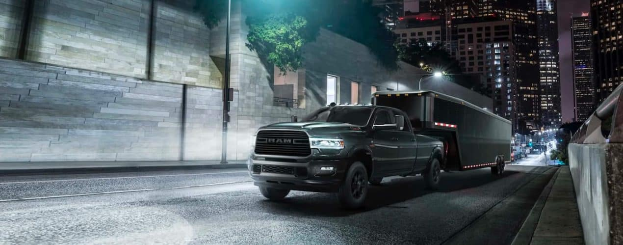 A black 2021 Ram 2500 Laramie is shown towing a enclose trailer through a city at night.