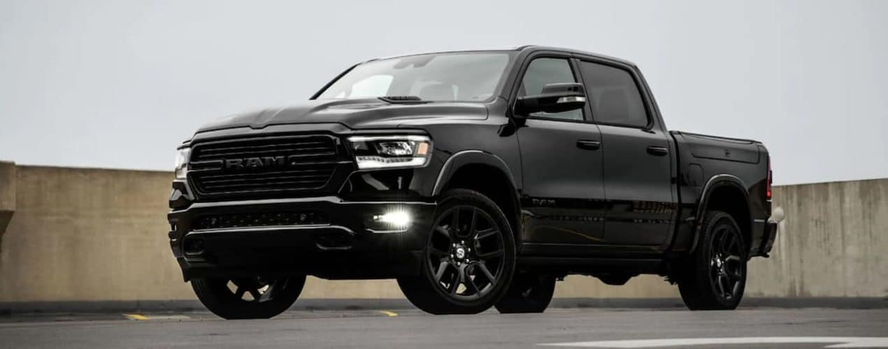A black 2021 Ram 1500 is shown from a low angle.