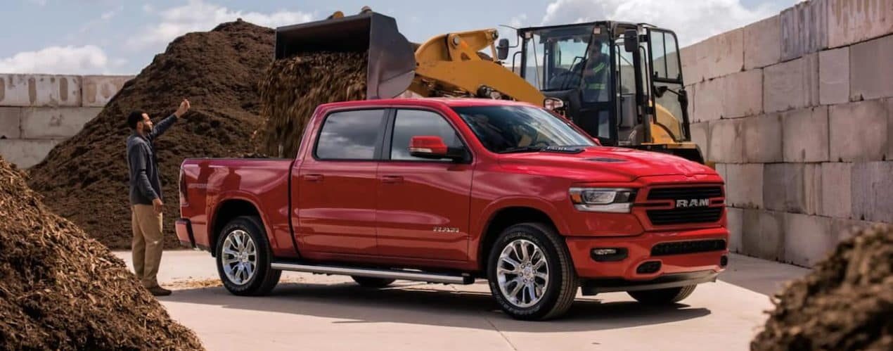 A red 2021 Ram 1500 is being used to haul wood chips at a construction site.