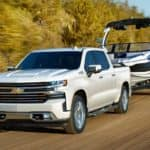 A white 2020 Chevy Silverado 1500 is shown towing a boat after leaving a Lexington used truck dealer.