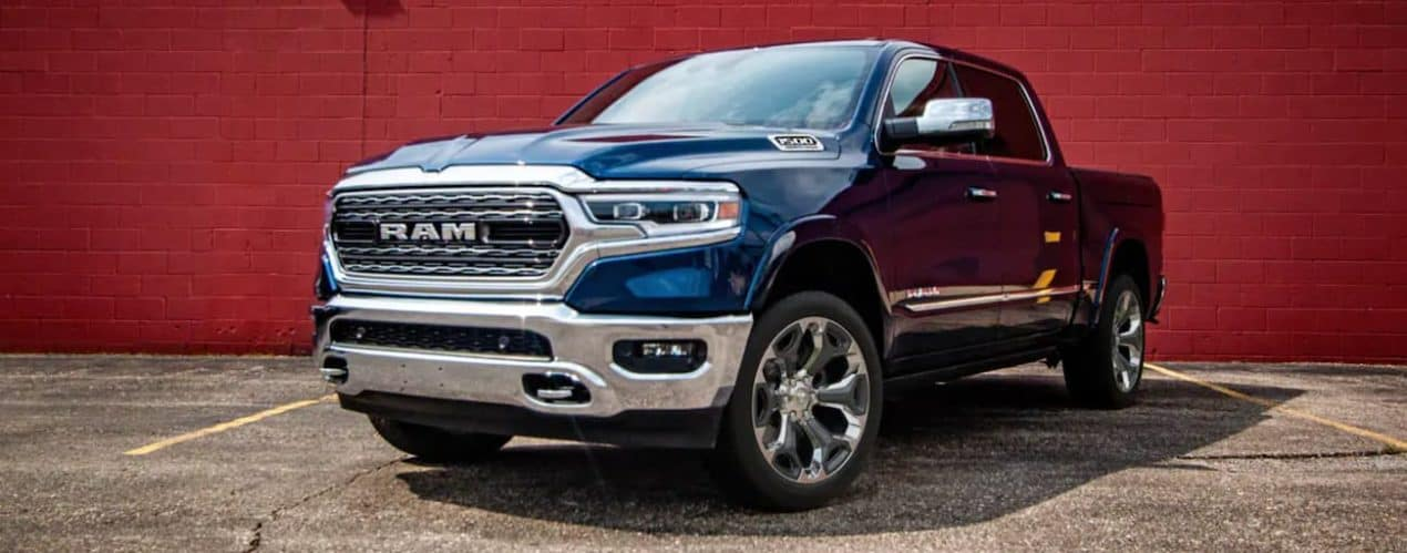 A blue 2021 Ram 1500 is parked in front of a red brick wall after winning a 2021 Ram 1500 vs 2021 Ford F-150 comparison.