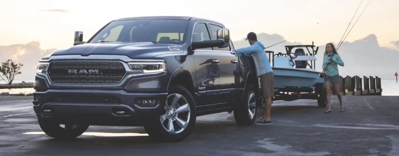 A grey 2021 Ram 1500 is towing a boat on a jetty.