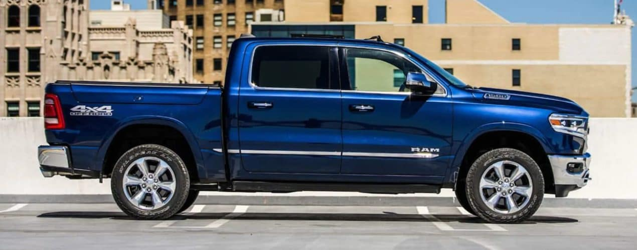 A blue 2021 Ram 1500 is shown from the side parked in a city after winning a 2021 Ram 1500 vs 2021 Chevy Silverado 1500 comparison.