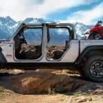A silver 2020 used Jeep Gladiator Rubicon is shown from the side with no doors in the mountains.