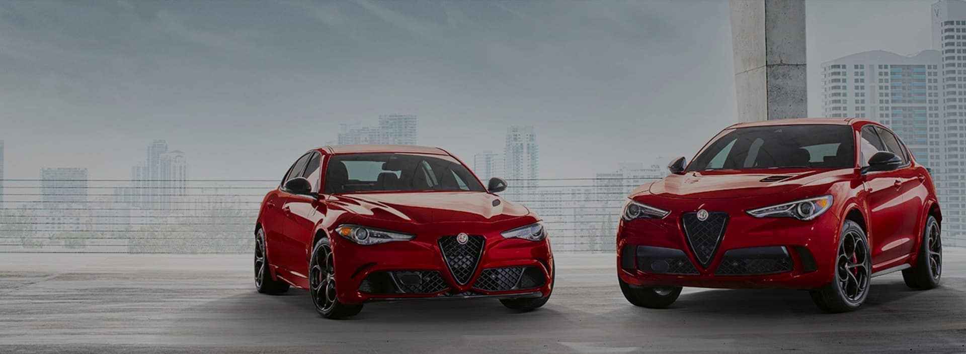 two red Alfa Romeo vehicles parked in front of a cityscape