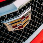 A closeup of the Cadillac logo on a red sedan