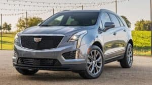A silver 2020 Cadillac XT5 under string lights facing left