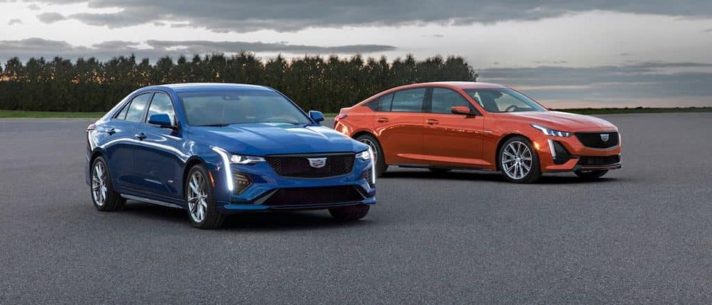 A blue 2020 Cadillac CT4 and an orange CT5-V, both available from a Cadillac Dealership in Fort Worth, TX, in an open lot at dusk.