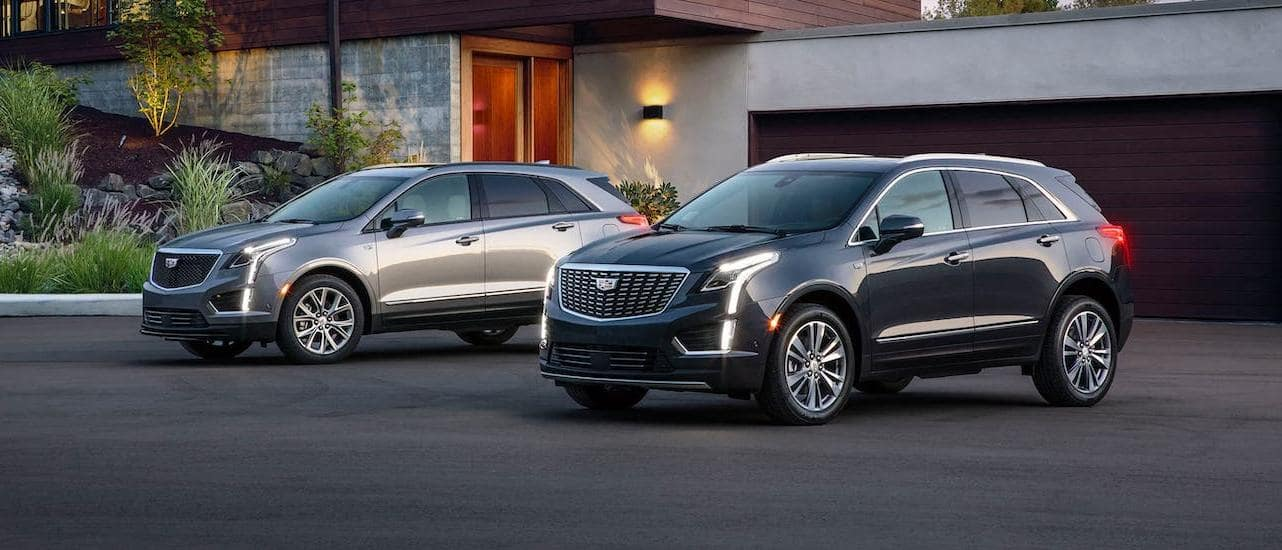 A silver and a black 2020 Cadillac XT5, both available from a Cadillac Dealership, in front of a modern house.