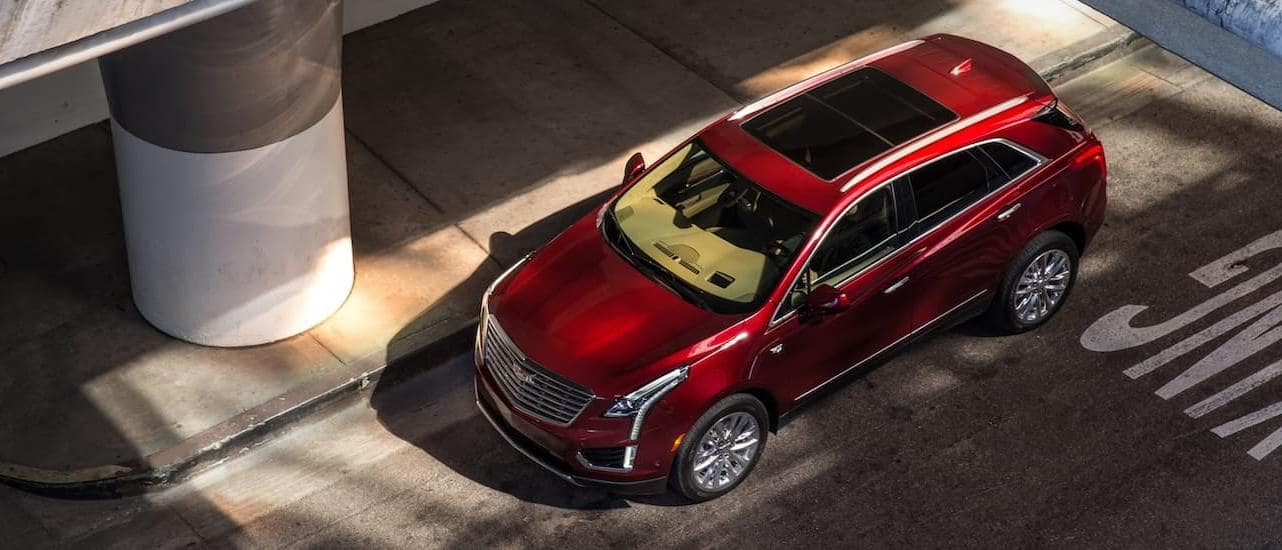 A red 2017 Cadillac Certified Pre-Owned XT5 is shown from above on a city road under a highway.