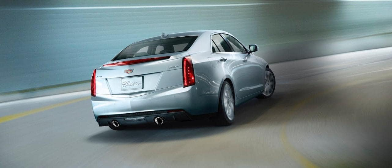 A silver 2020 Cadillac Certified Pre-Owned ATS is driving fast through a tunnel.