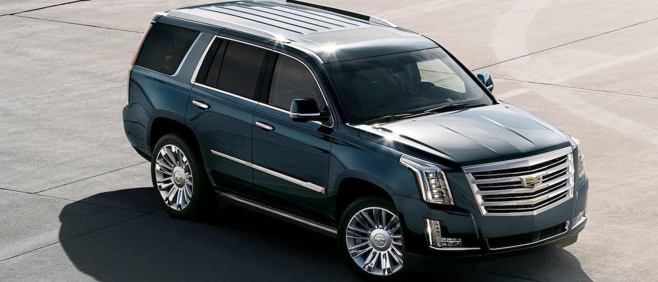 A blue/gray 2020 Cadillac Escalade is parked in an empty lot and shown from a high angle. Check one out at a Cadillac dealer near me.