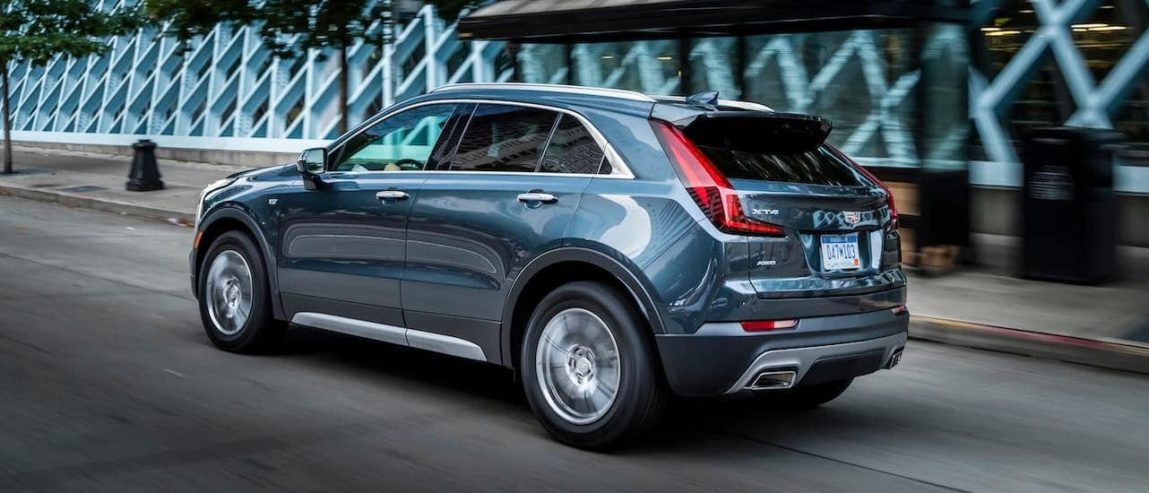 A gray 2020 Cadillac XT4 driving in a city.