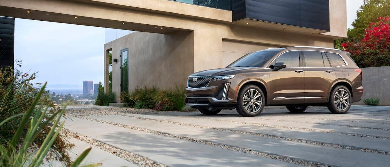 A brown 2020 Cadillac XT6 in front of a modern building.
