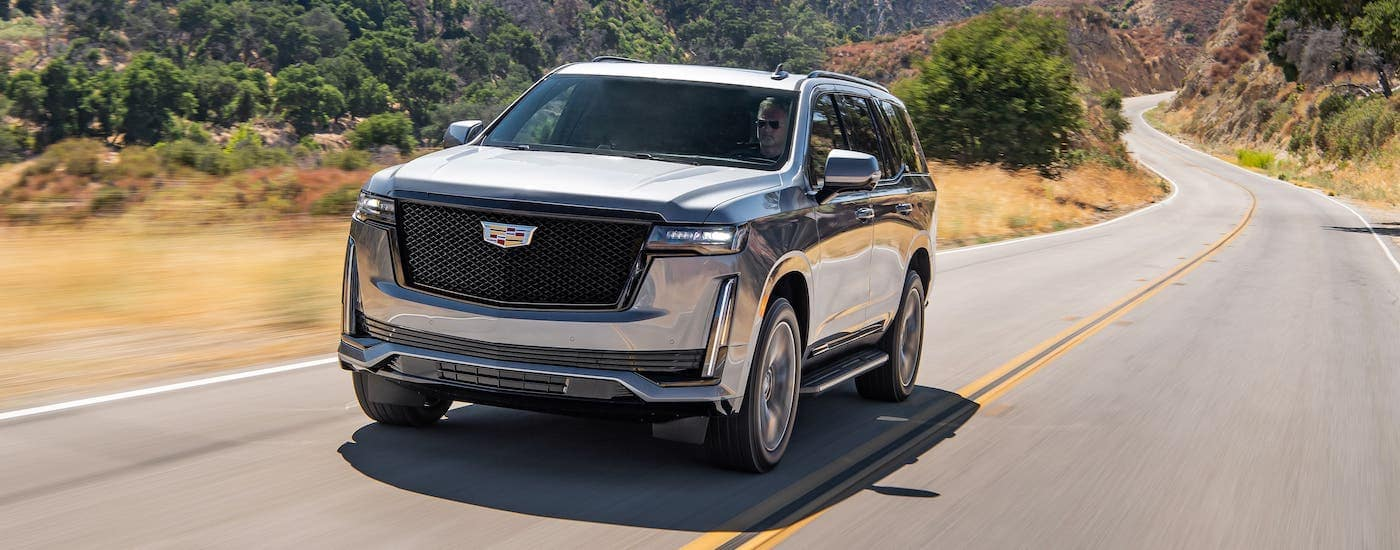 A gray 2021 Cadillac Escalade is driving on an empty highway.