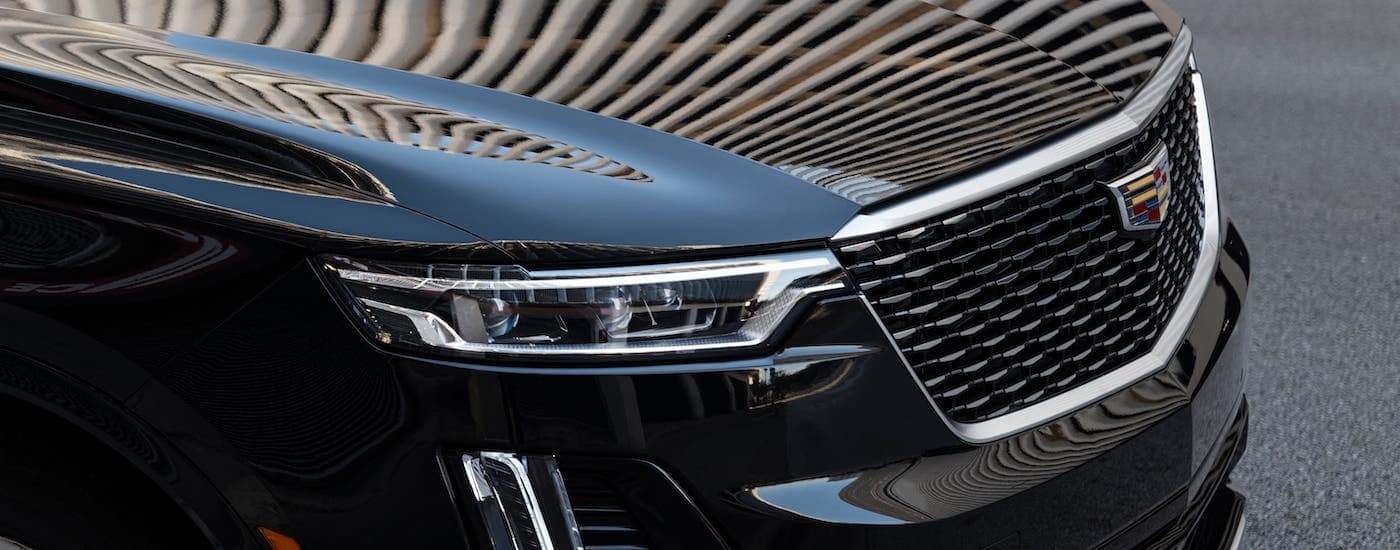 A closeup shows the hood and grille of a black 2021 Cadillac XT6.