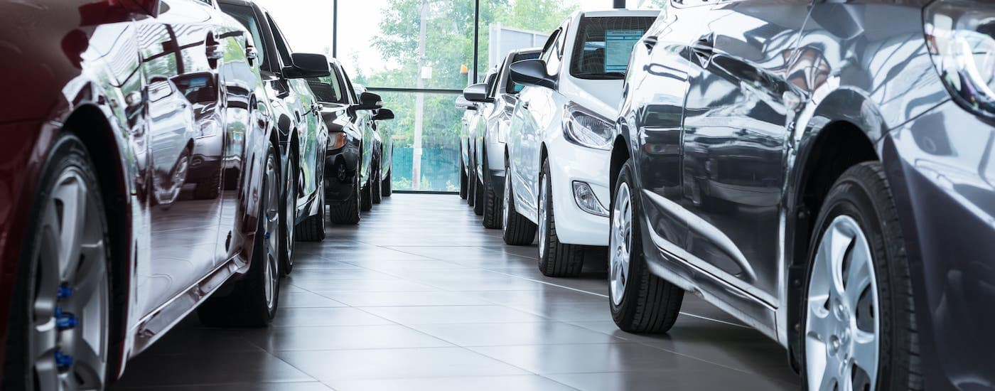 Multiple cars are shown inside a dealership that is offering Cadillac lease deals.