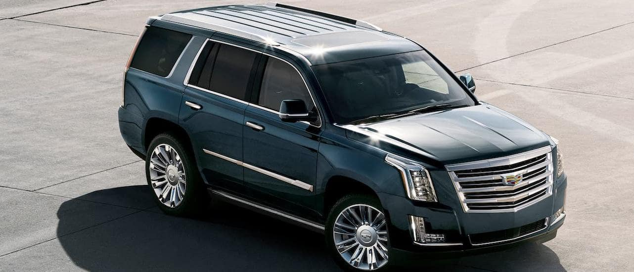 A dark gray 2019 Cadillac Escalade is a popular used luxury car and is angled right in an empty lot in Fort Worth, TX, shown from a high angle.