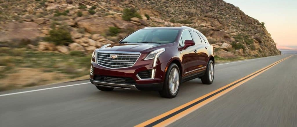 A red used luxury Cadillac XT5 driving around a mountain