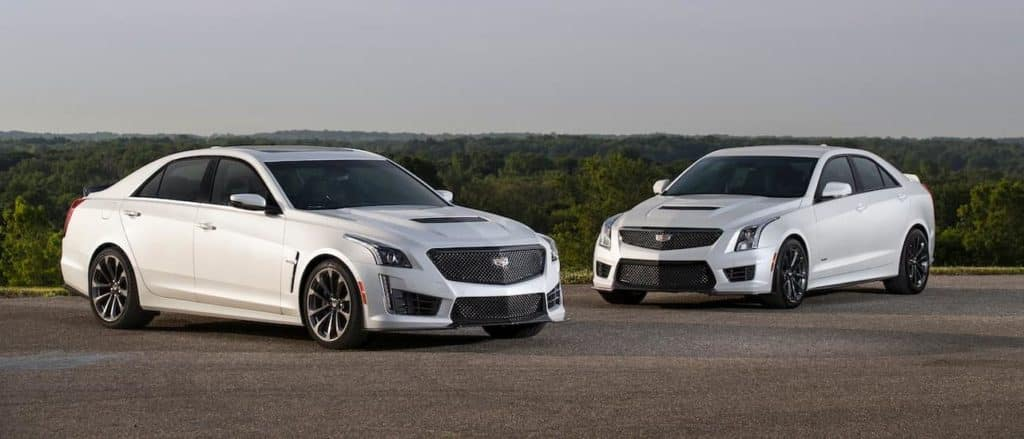 A white Cadillac ATS V and white Cadillac CTS V in front of a field near Fort Worth