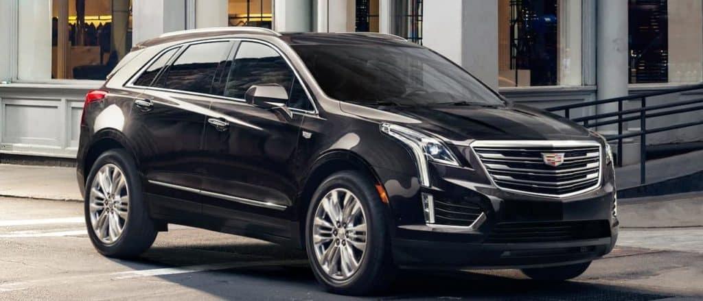 A black XT5 Cadillac for sale on a city street near Fort Worth, TX