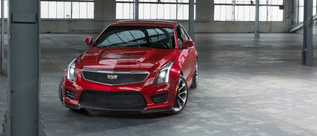A used red Cadillac ATS V in a warehouse available in Dallas