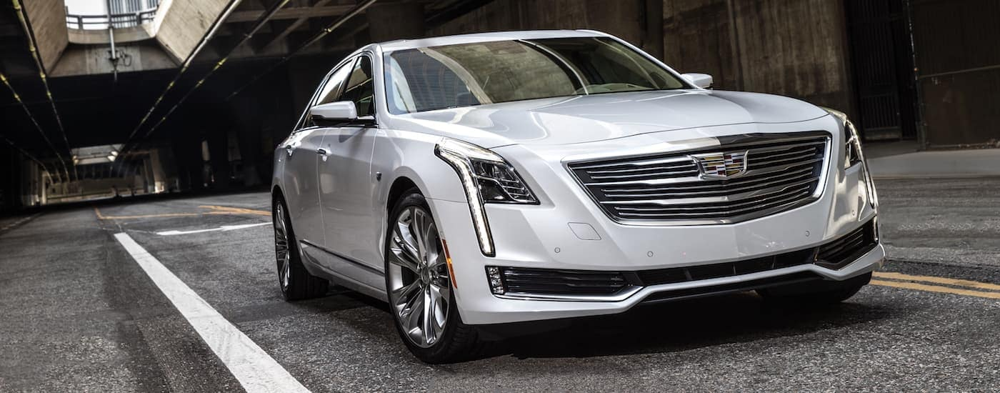 A silver 2017 pre owned Cadillac CT6 is on a city street with a highway over pass above near Fort Worth, TX.